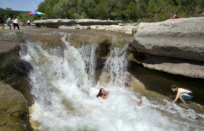 With Bull Creek flowing, people flock to the water to cool down and play.