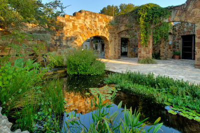 Visitors entering the grounds at the Lady Bird Johnson Wildflower Center see a wetland pond and Spanish mission-style archways that form an aqueduct for delivering rainwater.