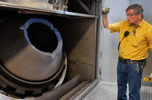 A staff member of AECOM  with the Anniston Static Detonation Chamber to be used at the PCAPP.
