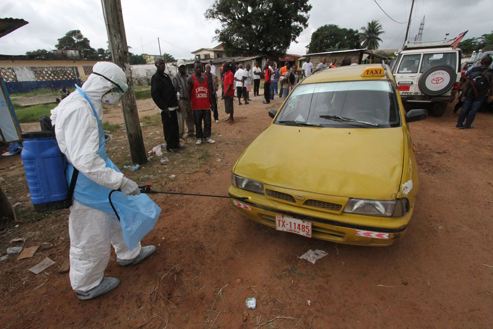 A health care worker disinfecting a taxi in Liberia at an Ebola treatment center.