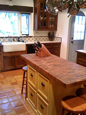 A butcher block countertop on a kitchen island creates a warm, classic focal point.