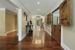 This long foyer has wooden barn doors that lead into the living room.