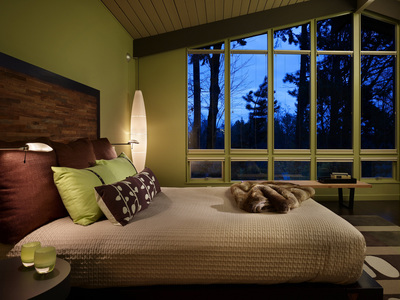 Floor-to-ceiling windows in the master bedroom stress the indoor-outdoor emphasis of the home.