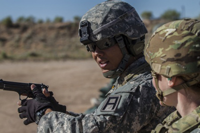 Army Reserve drill sergeant, Sgt. Robert Benavente, 95th Training Division (IET), provides some extra coaching to a Soldier preparing to deploy while firing the M9 at McGregor range in New Mexico.