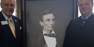 Illinois State Bar Association Third Vice President Dennis Orse, left, and 20th Judicial Circuit Chief Judge Andrew Gleeson flank the high-quality reproduction photo portrait of Abraham Lincoln.