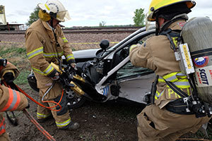 Firefighters practice extracting someone from a vehicle after a mock crash during the Chemical Stockpile Emergency Preparedness Program Exercise in May 2015.