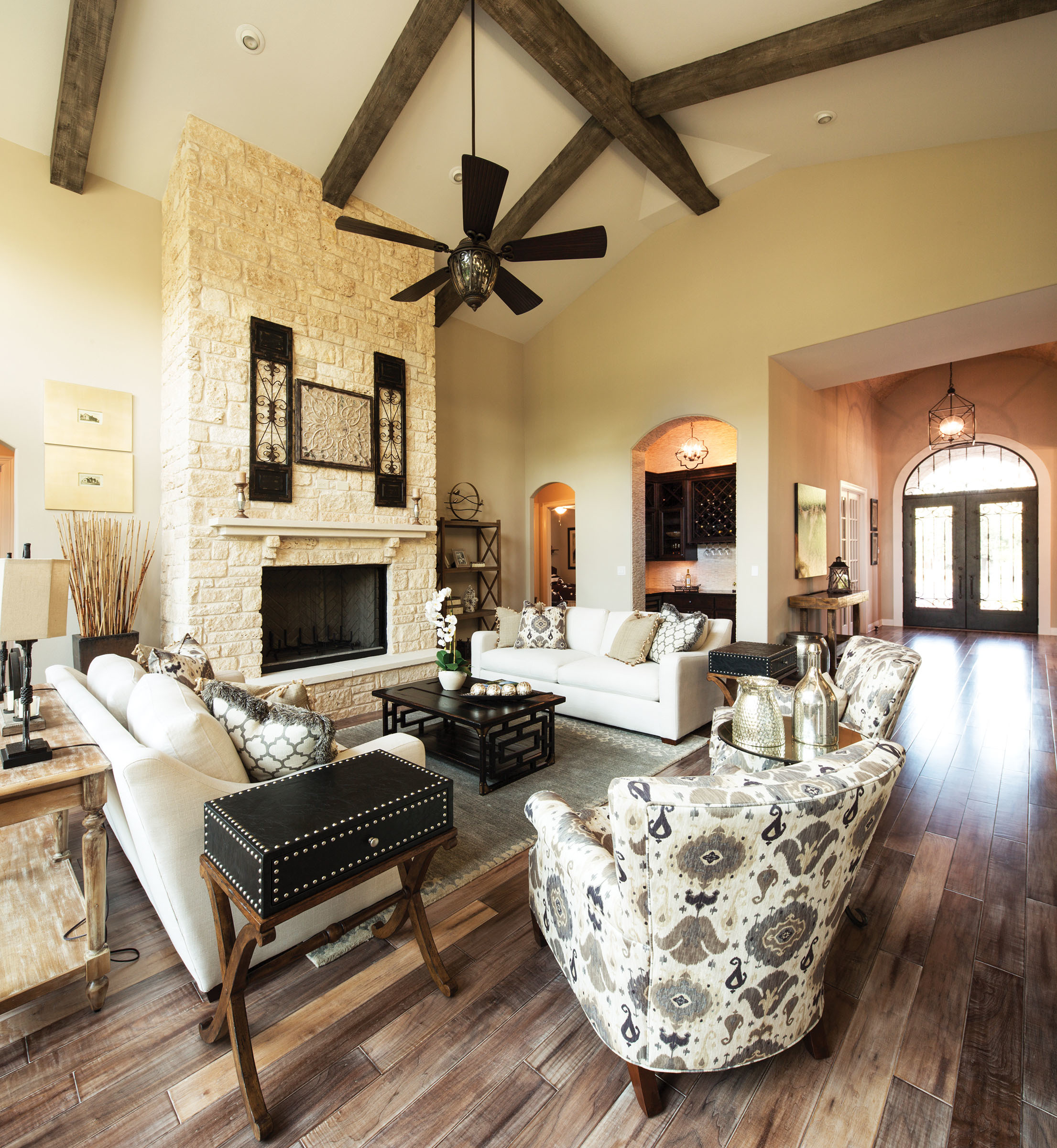 The available home on a meticulously manicured acre in Bella Montagna features a family room with large windows, an ornate ceiling and a floor-to-ceiling stone fireplace.