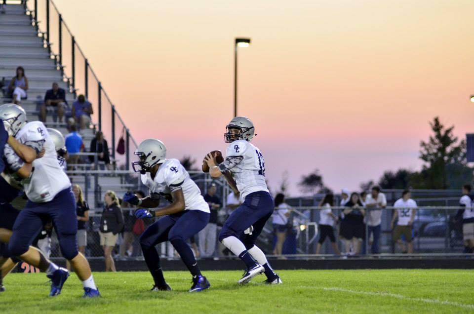 Oswego East's quarterback prepares to throw a pass