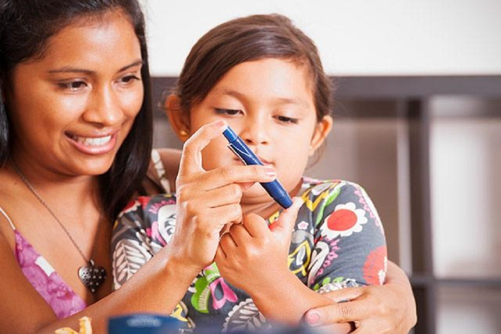 A parent helps a child monitor her blood sugar level.