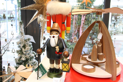A wooden holiday figurine that could be placed next to other wooden decorative items such as a jewelry box in a bedroom or next to cookbooks and cutting boards in the kitchen.