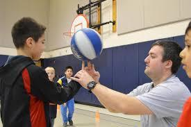 A camper works on spinning the ball on one finger with the help of an instructor.