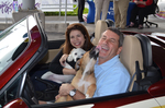 American Humane Society Executive Director Frances Jonon, left, and Jim Bagan enjoy a moment with two of their clients at Roger Beasely Mazda.
