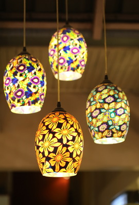 Bold, colorful hanging lamps are taking the place of chandeliers.