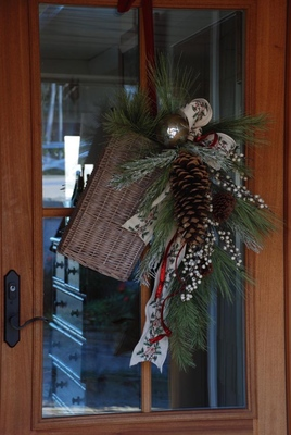 This door is dressed up in a upside-down bouquet made from tying together a bare twig, some pine cones and evergreen picks, and finished off with a plaid bow.