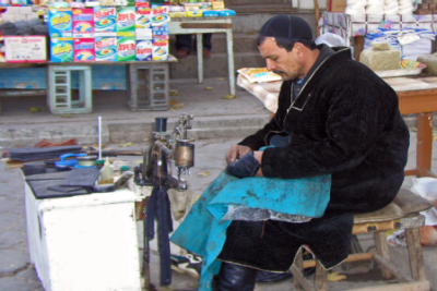A man repairs shoes near a market in Uzbekistan.