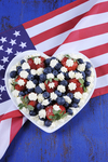 This dish of strawberries and blueberries with fresh cream stars in a white heart is great for an Independence Day party.