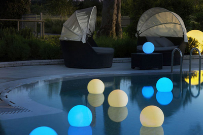 Spheres with glowing pastel colors floating about the pool create a bit of evening magic outdoors.