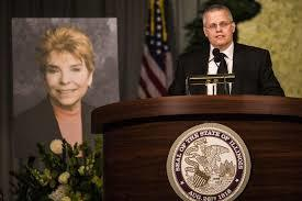 Joseph Baar Topinka stands in front of a picture of his mother.