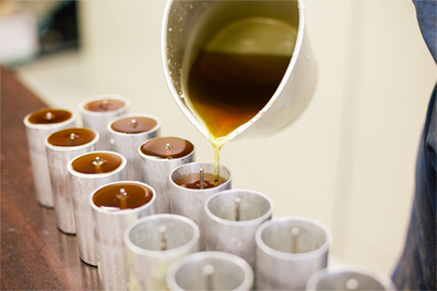 Wax is poured into candlestick molds at the Beeswax Co, an Austin area firm specializing in the clean-burning candles.