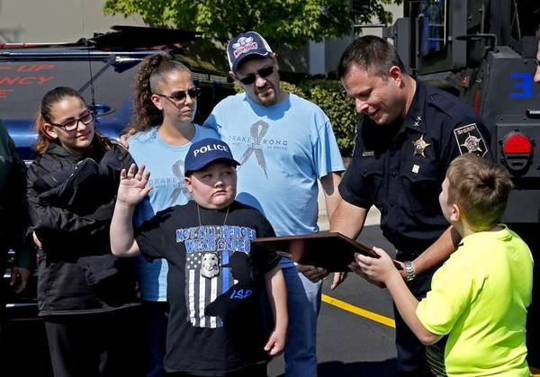 Eleven-year-old Drake Price, who is receiving treatment for a brain tumor, was sworn in as a junior DuPage County deputy for the day by Undersheriff Frank Bibbiano.