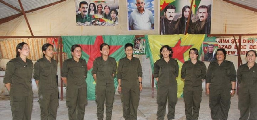Kurdish women fighters, in Syria, in front of photo of PKK founder Abdullah Ocalan