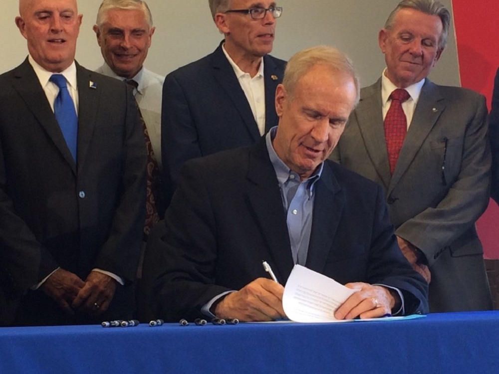 Gov. Bruce Rauner signs House Bill 2527 into law Friday in Rockford.