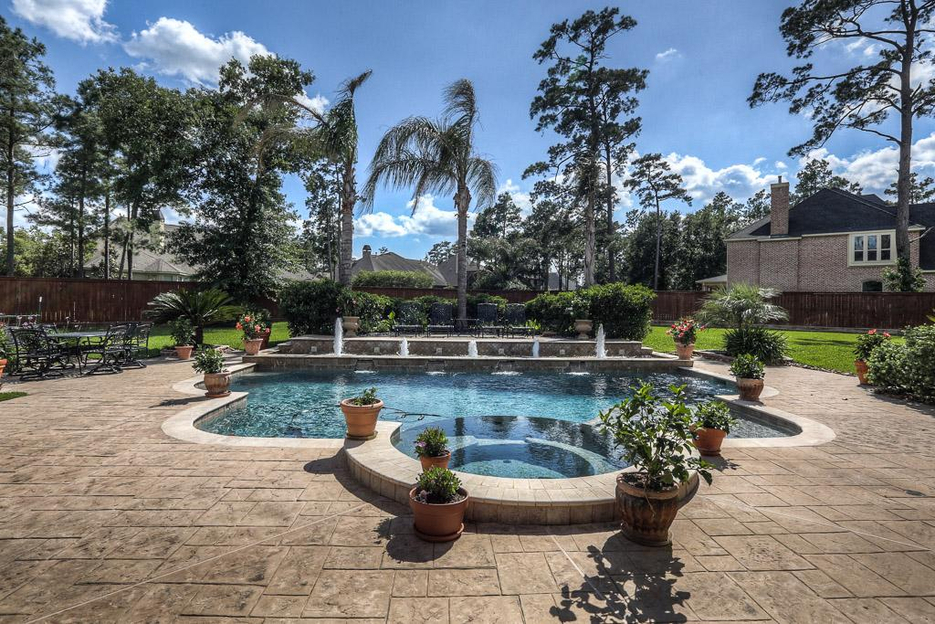 The large backyard features landscaping, a large patio, a pool with fountains and a spa.