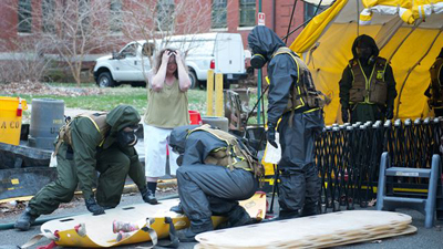 Marines from the decontamination platoon put a child pretending to be injured on a backboard during Exercise Silent Ghost outside St. Elizabeth's East Hospital in Washington, D.C. The exercise was a simulated chemical, biological, radiologic