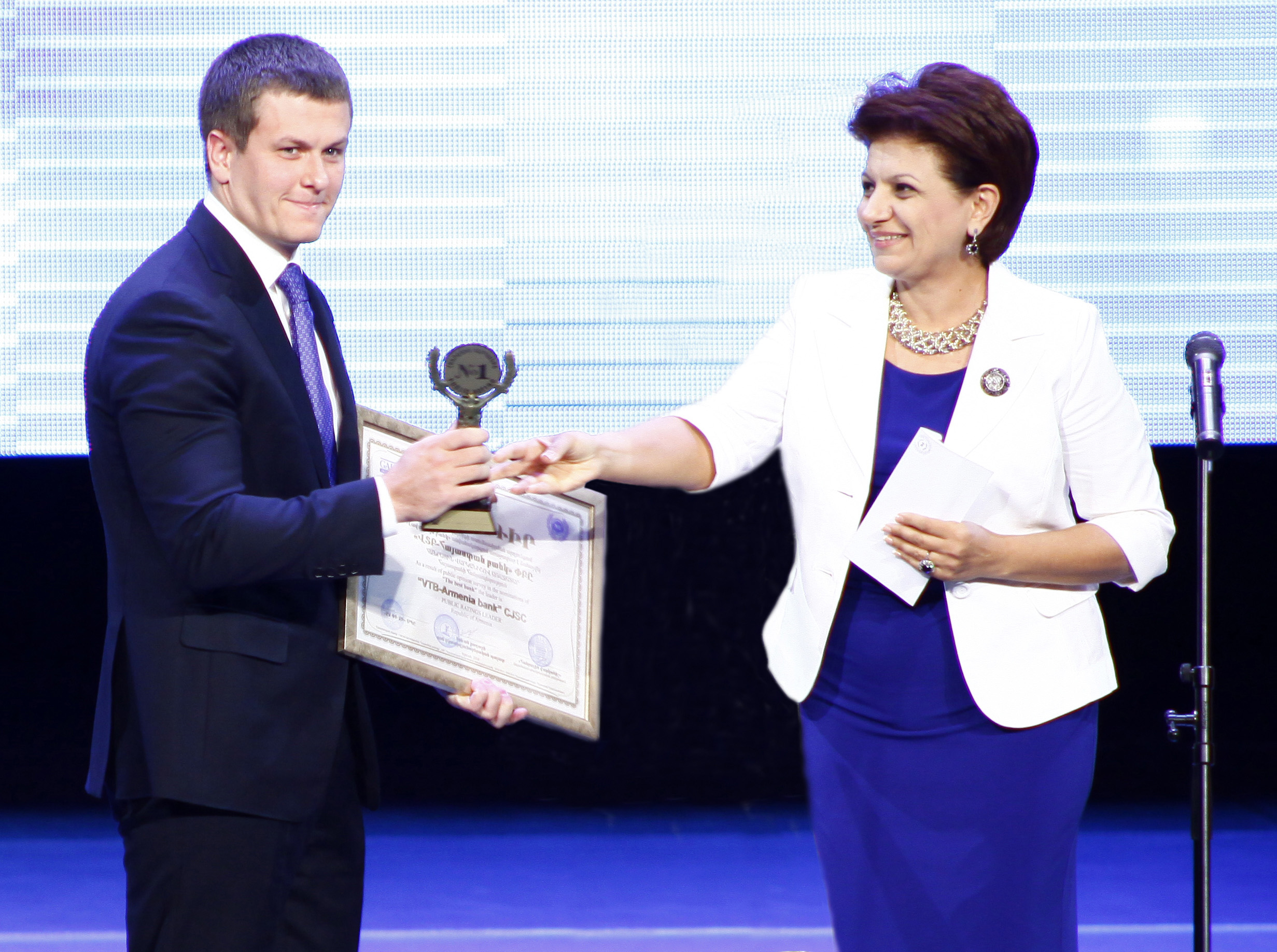 Yuri Gusev, left, of VTB Bank Armenia accepts the