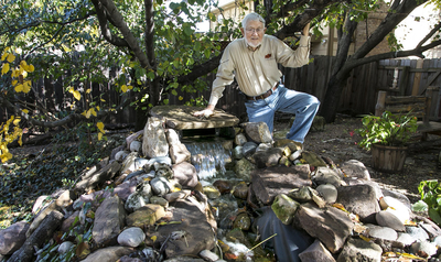 Lynn Jones is pictured on Nov. 17, 2015 with the waterfall he created in his backyard that helped him recover from heart surgery in WIchita, Kan.