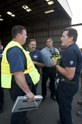 Kimo Kuheana, 92nd Civil Engineer Squadron fire chief, speaks with civilian counterparts on Aug. 12, 2015, after a chemical leak at the Pacific Steel and Recycling plant in Spokane, Wash.