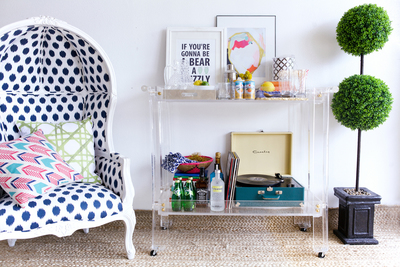 A Lucite bar cart creates convenient storage without being visually imposing.