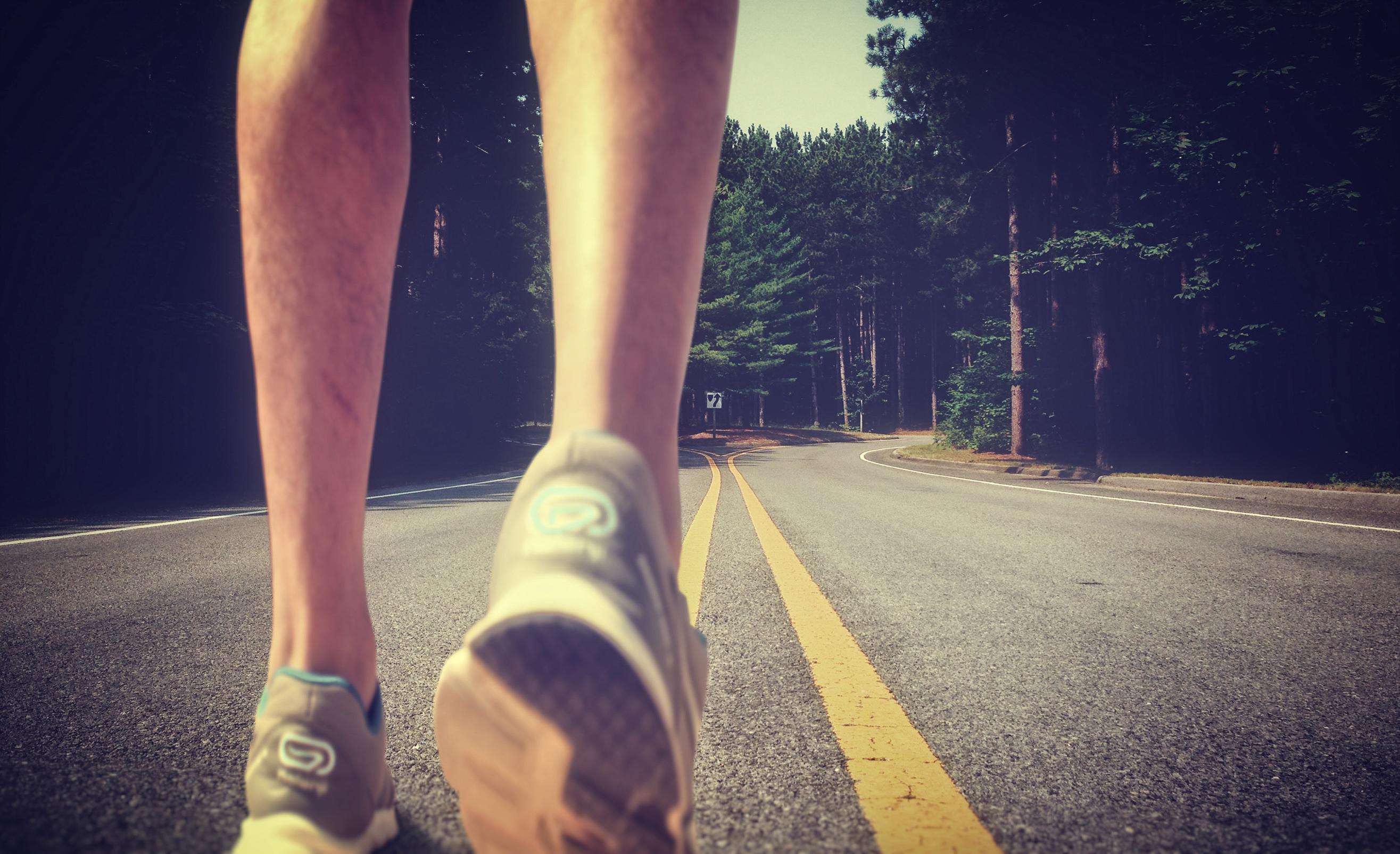 Stockvault feet of an athlete running on a deserted road179154