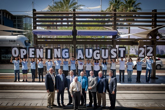Local officials pose in front of the Center/Main Street station with members from the Mayor's Youth Committee to reveal the Central Mesa extension's Aug. 22 opening date.