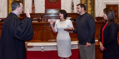 Kayla Kessinger is sworn in as a member of the West Virginia House of Delegates while her father Mike holds the Bible in this 2014 photo. Justice Allen Loughry swore her in, while her mother watches. (West Virginia Legislature photo)