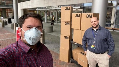 Yitzy Schleifer, left, accepting Powered Air Purifying Respirators from MileOne Autogroup.
