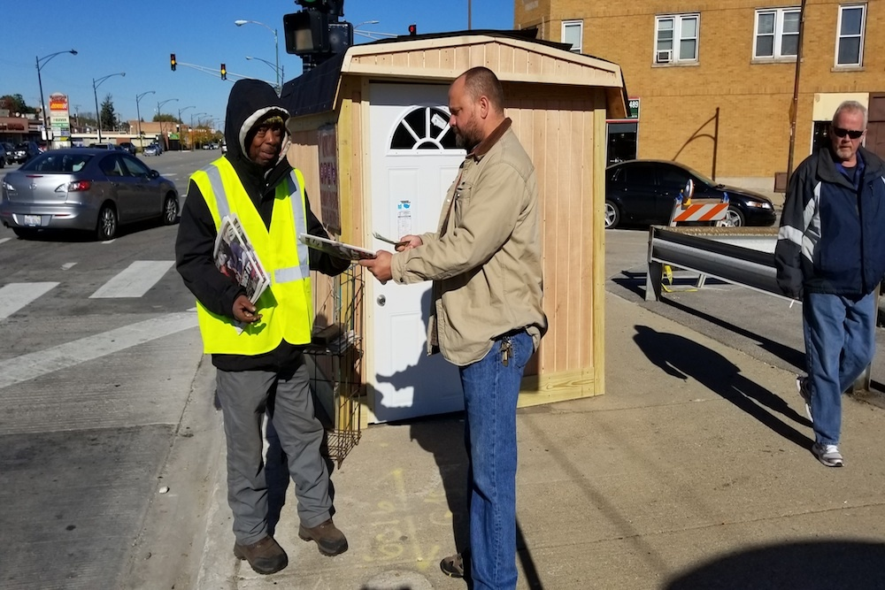 Anthony (left), a homeless veteran, handing papers out at the newsstand built through community donations in the Gladstone Park neighborhood.