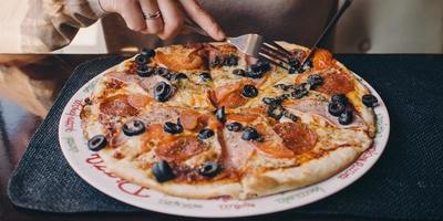 The average American consumes 23 pounds of pizza each year.