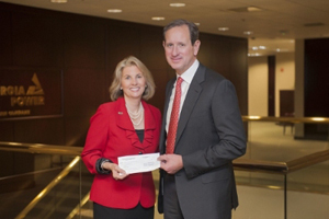 Georgia Public Broadcasting President and CEO Teya Ryan accepts a check recently for $500,000 from Georgia Power Chairman, President and CEO Paul Bowers to fund new educational programming.