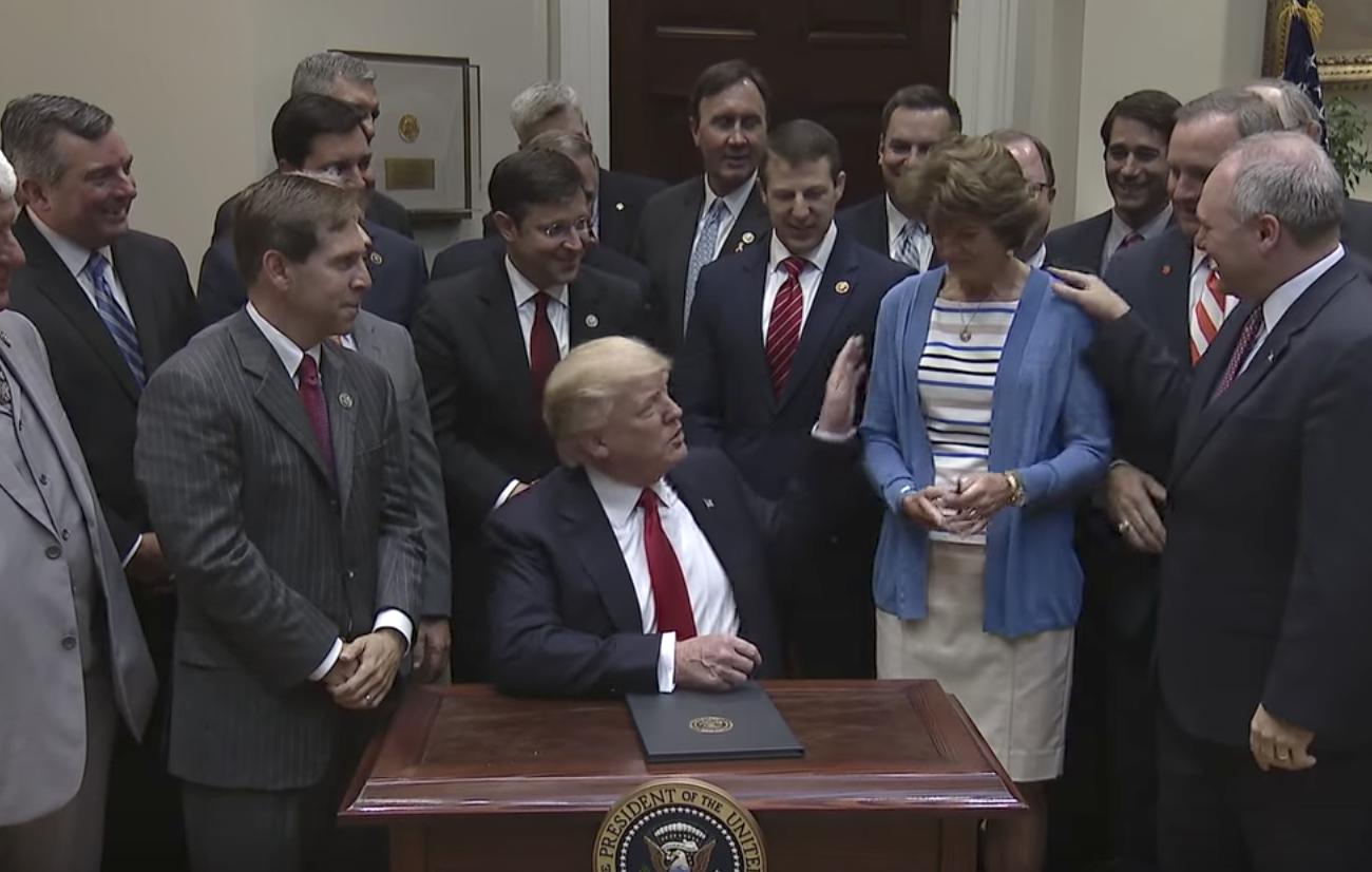 On April 28, 2017 President Donald Trump hands U.S. Sen. Lisa Murkowski (R-AK) his pen after signing an executive order to implement