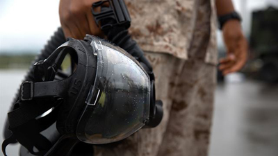 A Marine holds his gas mask after completing leak, seal, package and decontamination training April 21 at the gas chamber on Camp Hansen, Okinawa. Explosive ordnance disposal technicians and chemical, biological, radiological, nuclear defense specialists
