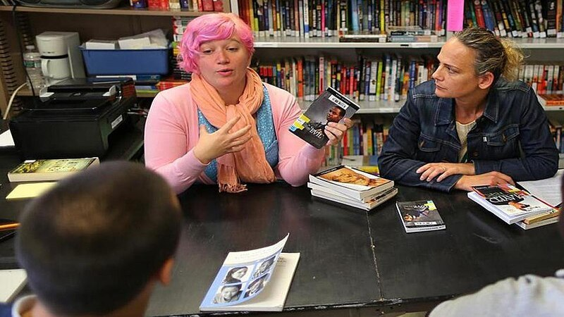 800px young adult librarian book talking with patrons 2