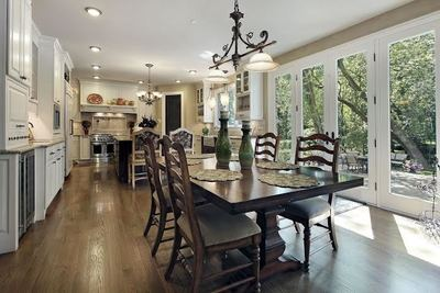 Large windows and patio doors let in natural light and brighten this dining area connected to a charming kitchen with state-of-the-art features.