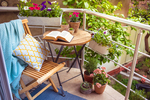 Plants, a rug, a bistro table are all ideal elements for a cozy balcony.