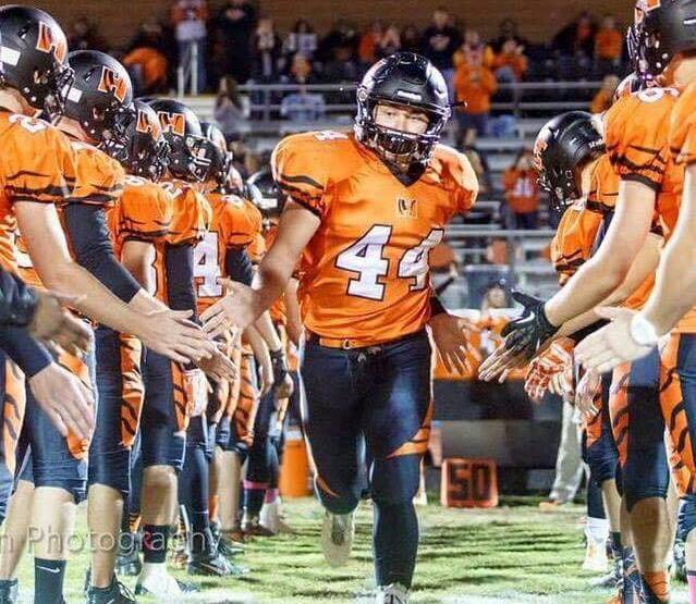 A Herrin High School player runs onto the field before a game.