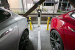 Two Tesla EVs charge at the City of Palo Alto EV charging station in a public garage in Palo Alto, Calif.