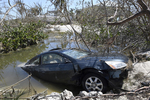 A flooded car in a hole filled with seawater in Big Pine Key, Fla., in 2017. Hurricanes Irma in Florida and Harvey in Texas last year left behind a large number of flood-damaged vehicles that are now appearing with a for sale sign.