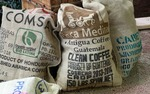 The coffee bags are kept out of the garbage and converted into tote bags, with fabric for the linings and handles.