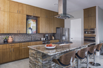 The contrast of rustic stone and shiny countertop displays an effective mixing of finishes.