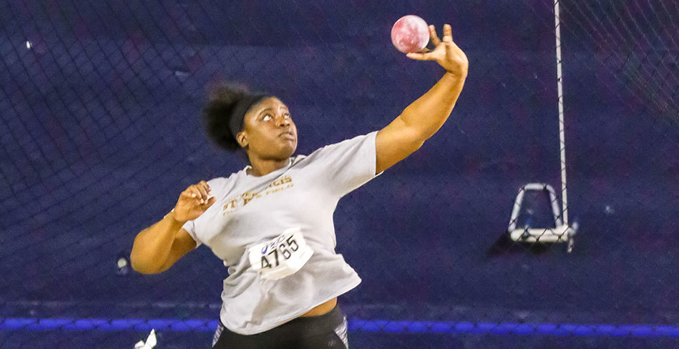 Raven Kelly throws the shot put at a meet.